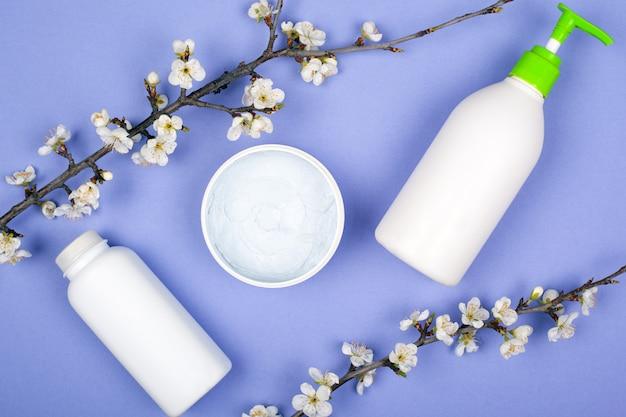 Piękno wiosny naturalne kosmetyki, krem z kwitnących gałęzi na fioletowym tle.