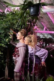 Piękno wokół nas. pozytywne, dobrze wyglądające kobiety patrzące na zielone rośliny, kochające przyrodę