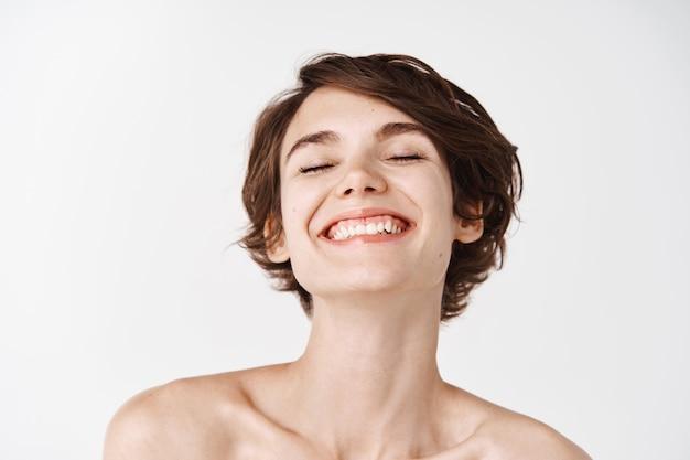 Piękno. zbliżenie pięknej i naturalnej dziewczyny z białym uśmiechem i roześmianymi nagimi ramionami, uśmiechniętej beztrosko. młoda kobieta bez makijażu pokazująca efekt po kosmetykach, biała ściana