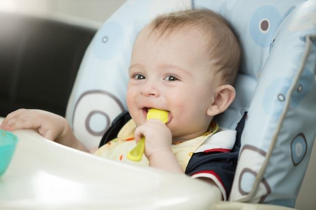 Piękny 9-miesięczny chłopiec bawi się łyżką podczas jedzenia