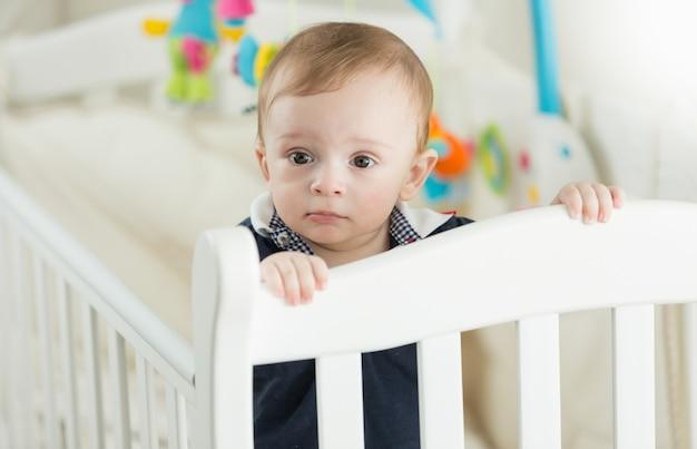 Piękny 9-miesięczny chłopiec stojący w białym łóżeczku