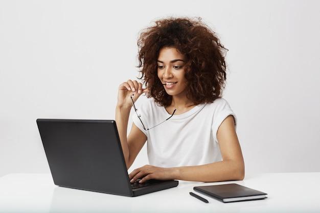 Piękny afrykański bizneswoman patrzeje laptopu ekran nad biel ścianą.