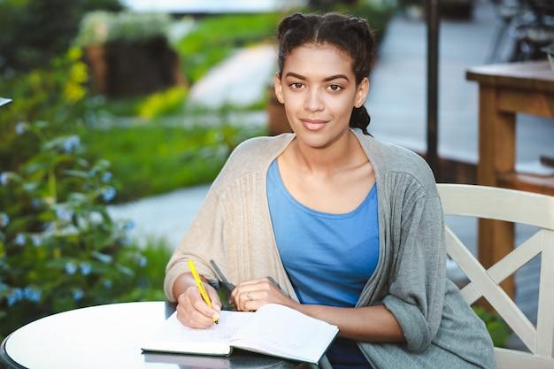 Piękny afrykański dziewczyny writing przy notatnikiem