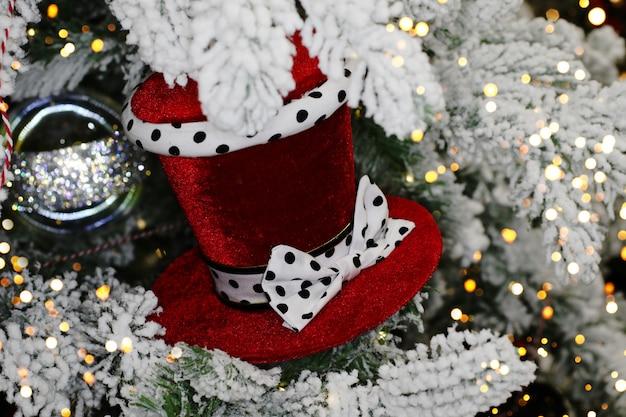 Piękny aksamitny kapelusz na gałęzi jodłyświąteczna zabawkaośnieżone gałęzie