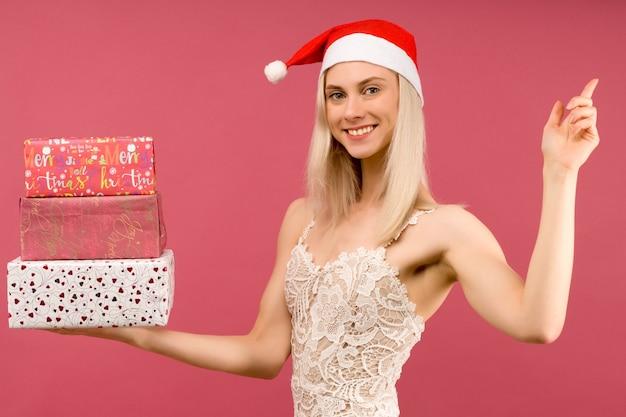 Piękny atletyczny transseksualny mężczyzna w noworocznym kapeluszu i białej sukni, trzymaj w rękach prezenty