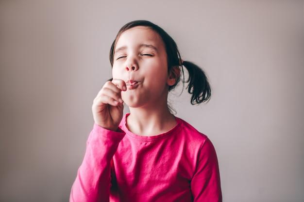 Piękny atrakcyjny dziecko odizolowywający nad ścianą. dziewczyna degustująca lizaka z przyjemnością i zamkniętymi oczami. ciesz się słodyczami.