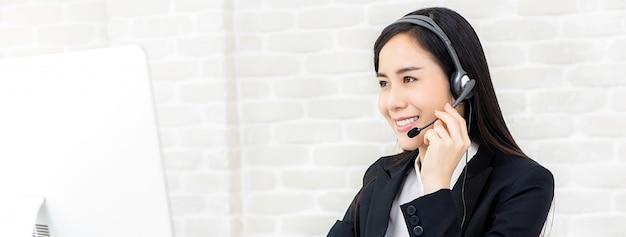 Piękny azjatycki bizneswoman pracuje w centrum telefonicznym jako operator