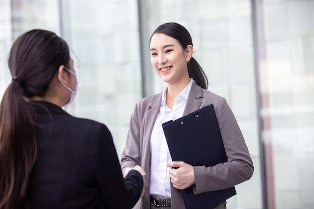 Piękny azjatycki chiński biznes kobieta drżenie rąk w nowoczesnym biurze pracy miasta.