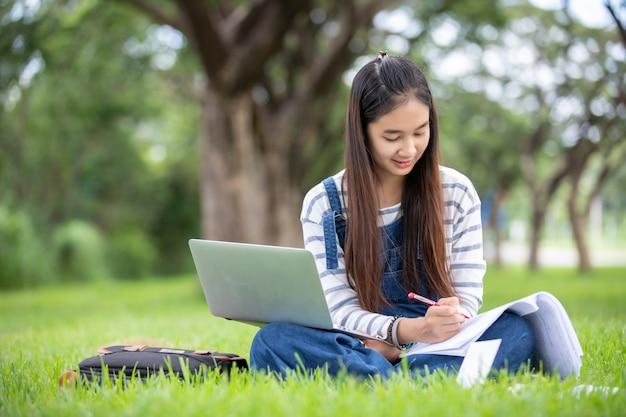Piękny azjatycki dziewczyna ucznia mienie rezerwuje, ono uśmiecha się, uczy się i edukacja na parku w lecie dla relaksuje czas