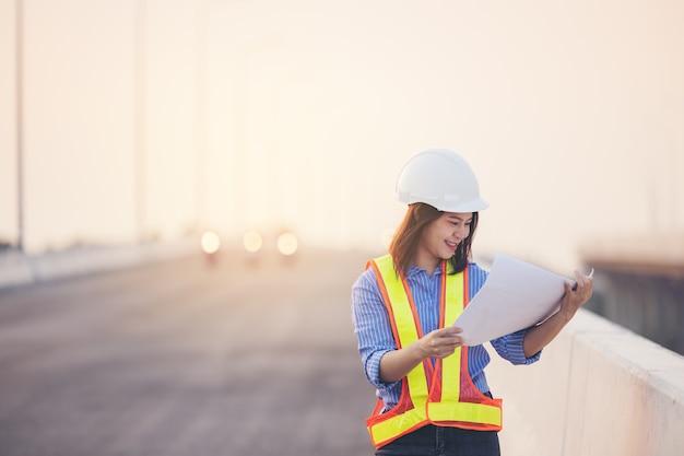 Piękny azjatycki inżynier kobieta w biały kask robi pracę na budowie poza biurem. pomysł na autostradę nowoczesnej kobiety pracującej