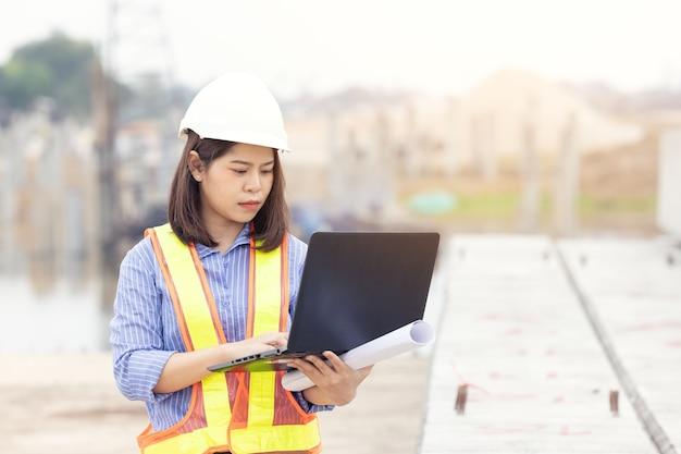 Piękny azjatycki inżynier kobieta w biały kask za pomocą laptopa wykonuje pracę na budowie poza biurem. pomysł na nowoczesną kobietę pracującą.