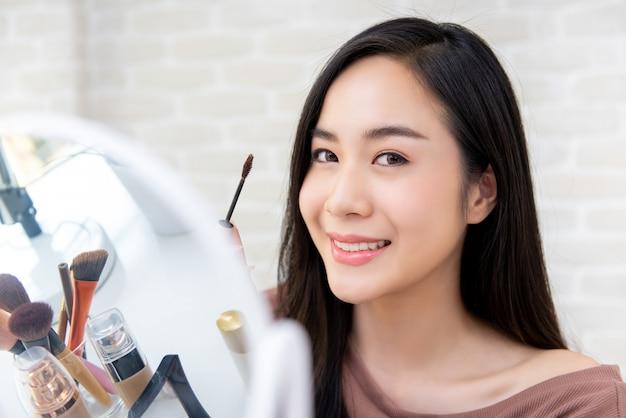 Piękny azjatycki kobiety piękna vlogger robi makeup tutorialowi