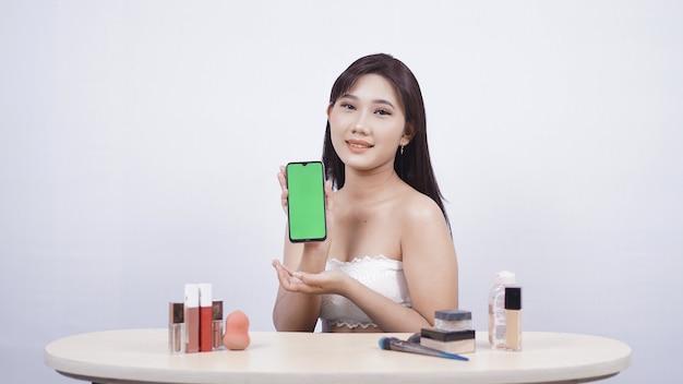 Piękny azjatycki makijaż pokazujący ekran smartfona na białym tle