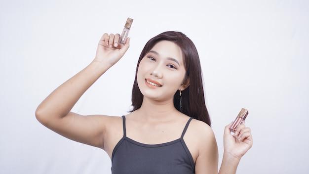 Piękny azjatycki makijaż pokazujący szminkę na obu rękach na białym tle