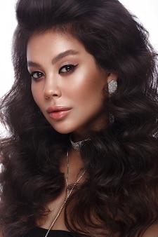 Piękny azjatycki model brunetki z lokami o dużej objętości, klasycznym makijażem i seksownymi ustami