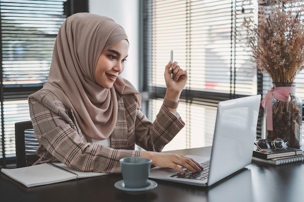 Piękny azjatycki muzułmański biznes kobieta brązowy hidżab siedzi i pracuje z laptopem w nowoczesnym biurze.