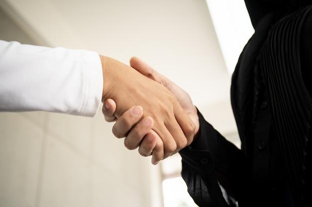 Piękny azjatycki muzułmański bizneswoman uścisk dłoni z jej kolegą