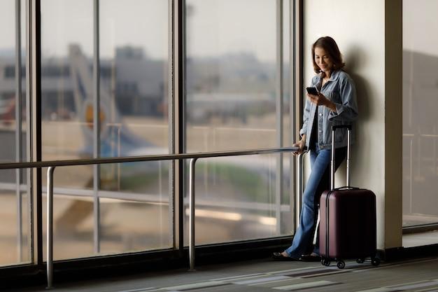Piękny azjatycki podróżnik stojący samotnie i przy użyciu smartfona na lotnisku, czekając na lot.