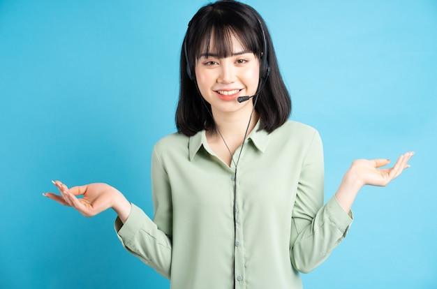 Piękny azjatycki żeński pracownik obsługi klienta ma na sobie słuchawki