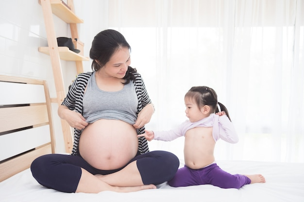 Piękny azjatykci ciężarny i jej córka pokazuje ich brzucha na łóżku