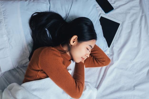 Piękny azjatykci kobiety dosypianie w łóżku.