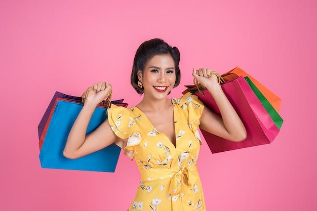 Piękny azjatykci kobiety mienie barwił torba na zakupy