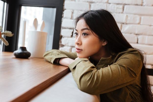 Piękny azjatykci młodej kobiety obsiadanie przy kawiarnią.