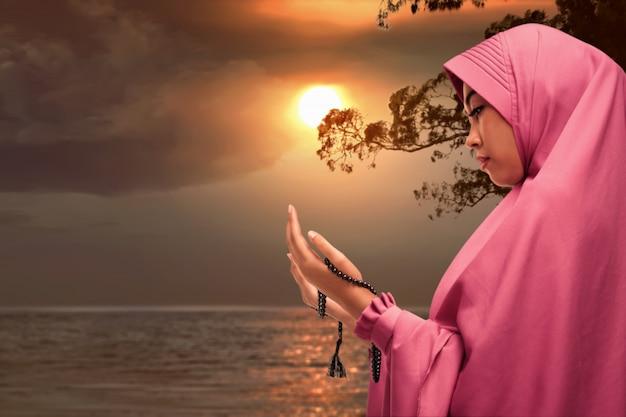 Piękny azjatykci muzułmański kobiety modlenie z modlitewnymi koralikami