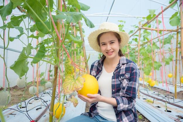 Piękny azjatykci rolnik trzyma świeżego melon od jej organicznie gospodarstwa rolnego i ono uśmiecha się.