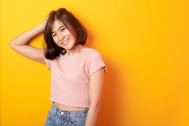Piękny azjatykci studencki szczęśliwy na kolor żółty ścianie
