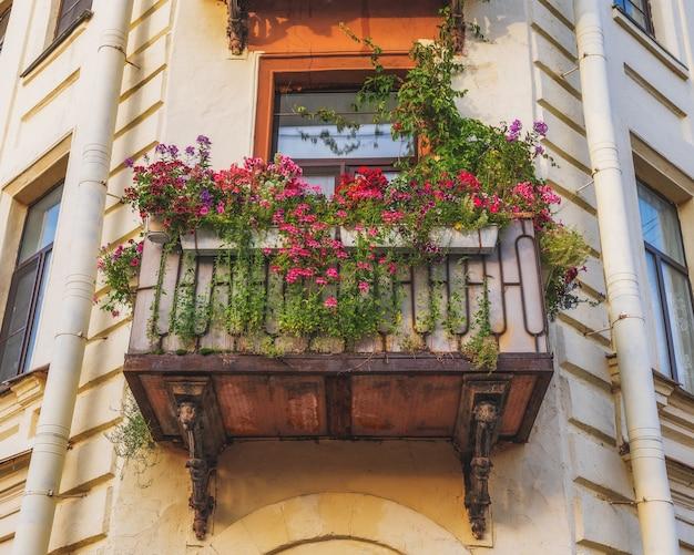 Piękny balkon vintage z kolorowymi kwiatami i brązowymi drzwiami