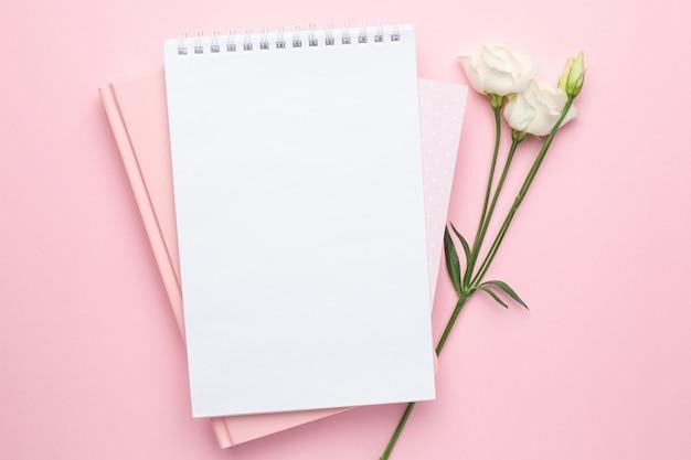 Piękny biały kwiat i notatnik na różowo