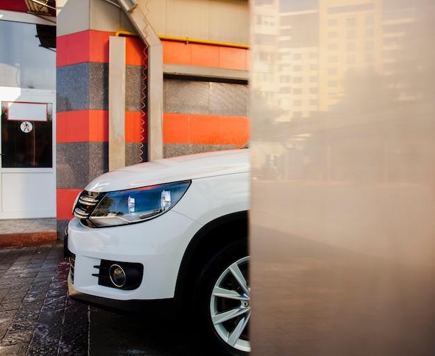 Piękny biały samochód opuszczający myjnię samochodową