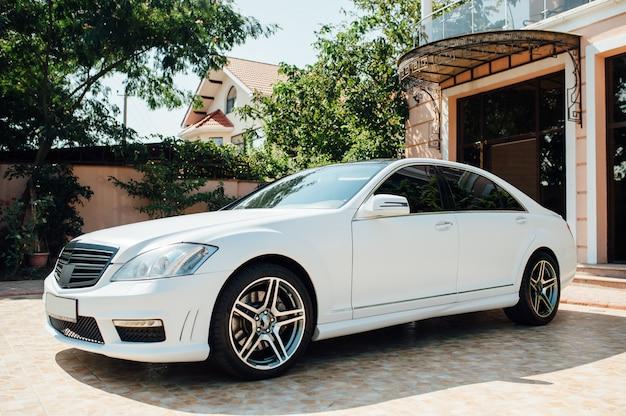 Piękny biały samochód zaparkowany w pobliżu domu