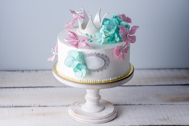 Piękny biały tort ozdobiony różowo-turkusowymi kwiatami i koroną księżniczki