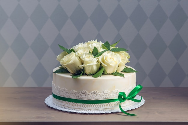Piękny biały tort weselny ozdobiony bukietem kwiatów białych róż