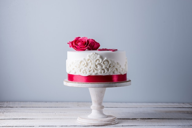 Piękny biały tort weselny ozdobiony kwiatami, czerwonymi różami i wstążką