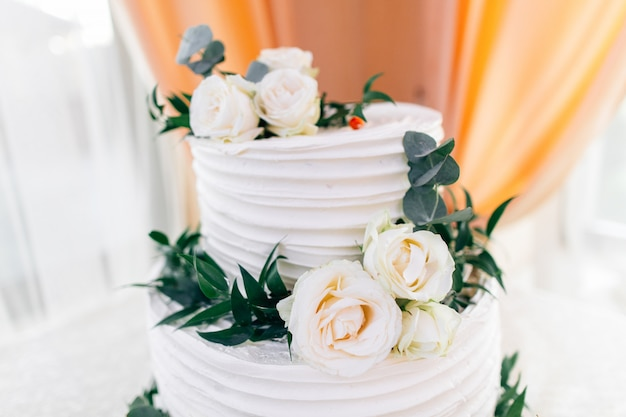 Piękny biały tort weselny ozdobiony kwiatami