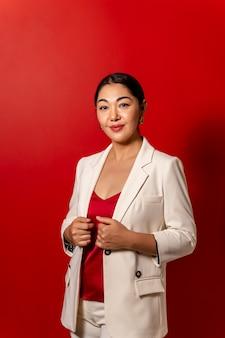 Piękny biznes azjatycka dziewczyna w białej kurtce na czerwonym tle.