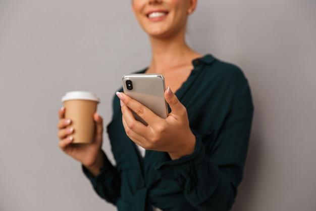 Piękny biznes kobieta pozowanie na białym tle nad szarym tle ściany picia kawy rozmawia przez telefon komórkowy.