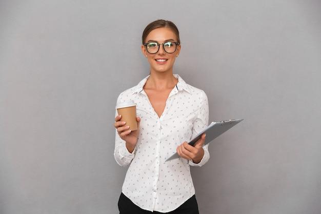 Piękny biznes kobieta stojąc na szarym tle ściany trzymając schowek do picia kawy.