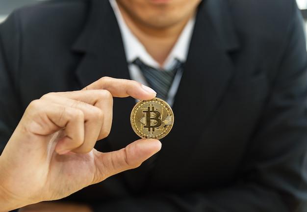 Piękny biznesowy mężczyzna model trzyma bitcoin złocistą monetę. crypto mining farm. handlowcy i giełdy,