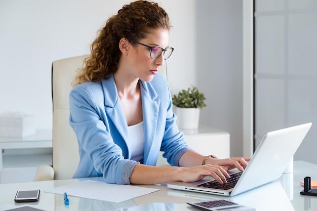 Piękny bizneswoman pracuje z jej laptopem w biurze.