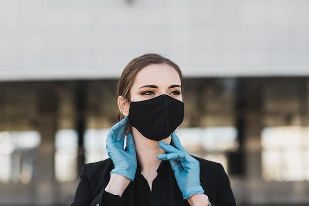 Piękny bizneswoman w czarnym kostiumu w czarnej medycznej masce i rękawiczkach przy miastem w kwarantannie i odosobnieniu. pandemia covid-19. selektywne ustawianie ostrości