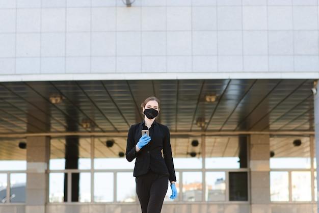 Piękny bizneswoman w czarnym kostiumu w czarnej medycznej masce i rękawiczkach przy miastem w kwarantannie i odosobnieniu. pandemiczny covid-19. selektywne ustawianie ostrości