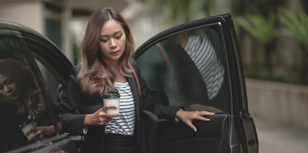 Piękny bizneswoman wychodzi z nowożytnego luksusowego samochodu podczas gdy trzymający filiżankę kawy