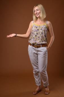 Piękny bizneswoman z blondynem pokazuje copyspace
