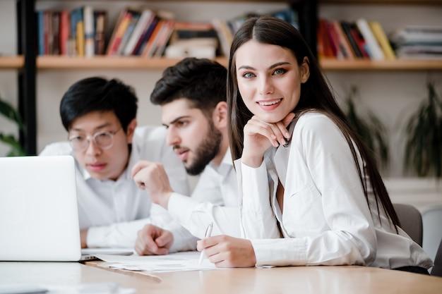 Piękny bizneswomanu obsiadanie przy biurkiem z dokumentami i laptopem z współpracownikami