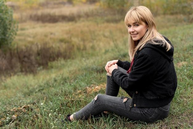 Piękny blondynki kobiety obsiadanie w naturze