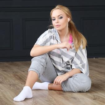 Piękny blondynki obsiadanie na drewnianej podłoga